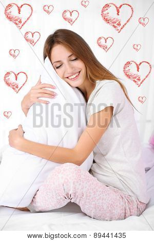 Beautiful young woman dreaming about love and sitting on bed