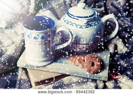 Cup of tea and teapot with cookies on plaid background