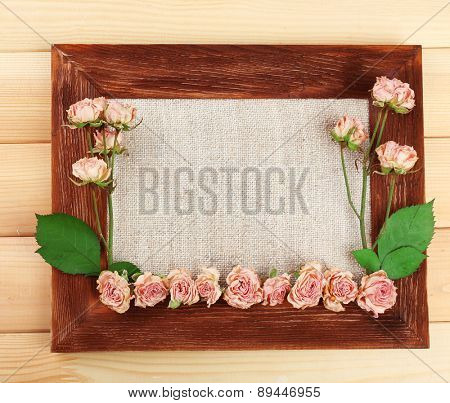 Frame of beautiful dry flowers with frame on wooden background