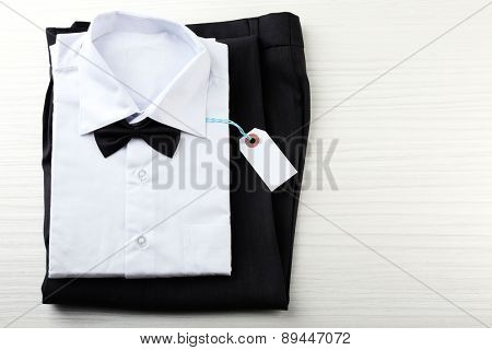 Price tag on white shirt, trousers on wooden background