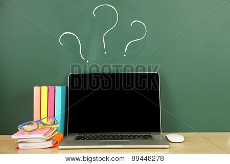 Laptop on table, on green blackboard background