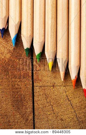 Wooden colorful pencils on wooden table