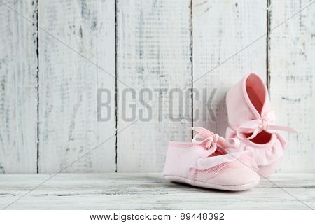 Pink toddler shoes on wooden background