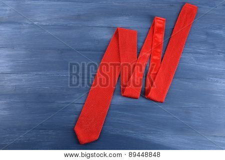 Red male tie on color wooden table background