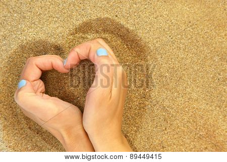 Hands hugging the sand in shape of heart