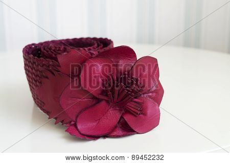 Red Flower-buckled Waist Band Lying On Table