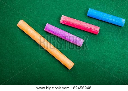 Four Pieces Of Chalk On Green