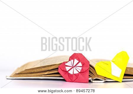 Open favorite literature with two origami hearts. Isolated.