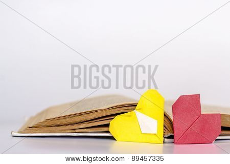 Open favorite literature with two origami hearts - red and yellow. I
