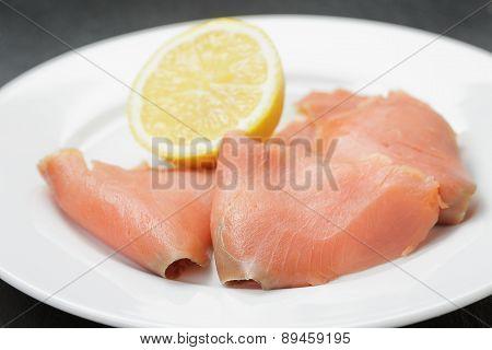 rolls of sliced smoked salmon on slate board