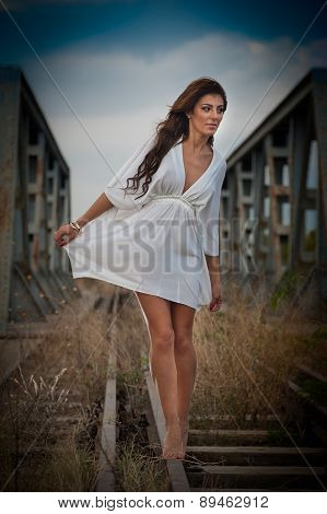 Sensual girl with white dress walking on the railway under the blue sky