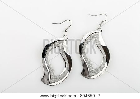 Pair of silver earrings on gray background