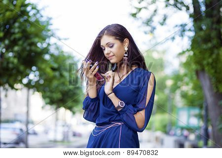 Young woman reading a message on the phone in a summer park