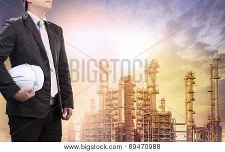 Engineering Man With Safety Helmet Standing Against Oil Refinery Plant In Heavy Petrochemical Indust