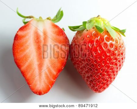Two strawberries and a half on a white background