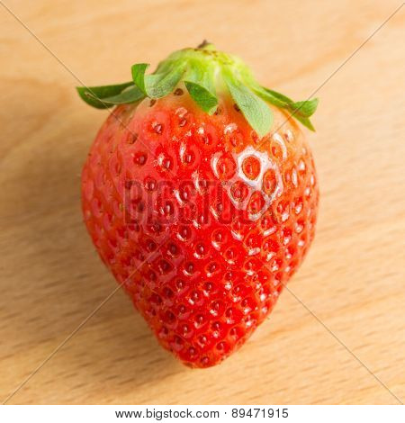 A single strawberry on a wooden cutting board