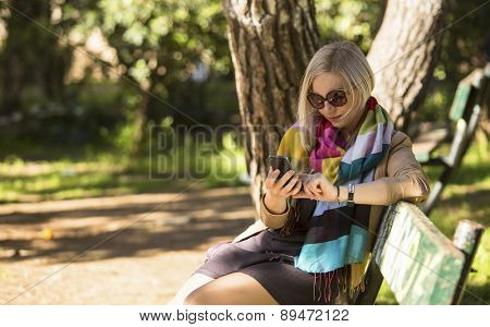 Young woman sitting on a Park bench and typing on her smartphone.