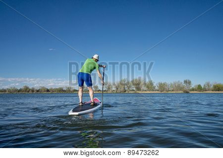 Senior male exercising on stand up paddling (SUP) board.. Early spring on calm lake in Fort Collins, Colorado..