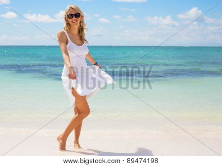 Young happy woman in white dress on the beach
