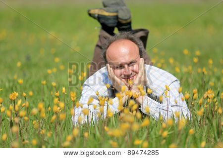happy man in yellow wild flowers on meadow