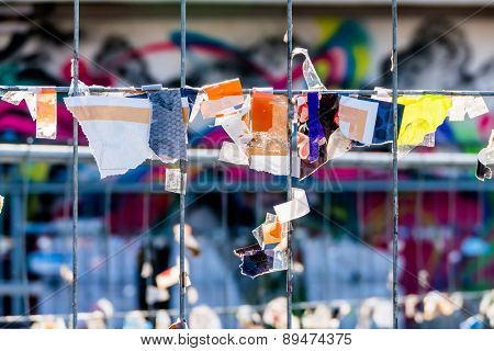 scraps of paper against a wire fence, symbolizing creativity, disorder, protest,