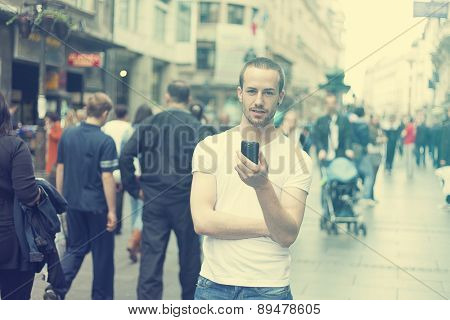Young Man in city with mobile phone walking, background is blured city street