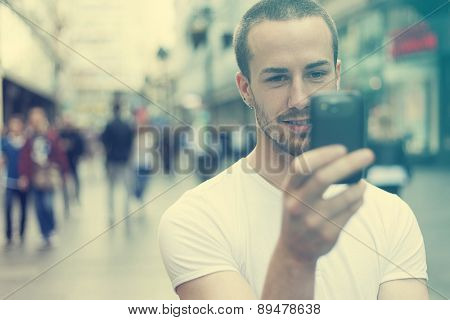 Young Man with mobile phone walking, background is blurred city