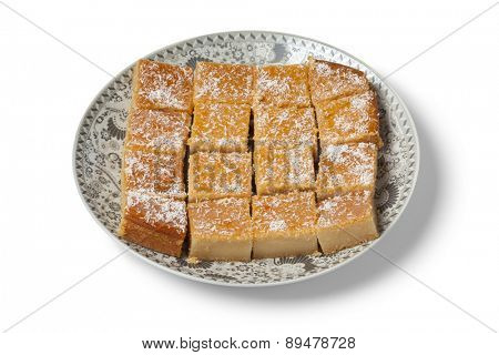 Fresh baked Moroccan yogurt cake cut into pieces on white background
