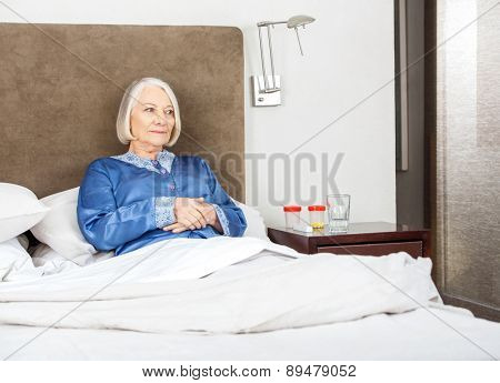 Thoughtful senior woman relaxing on bed at nursing home