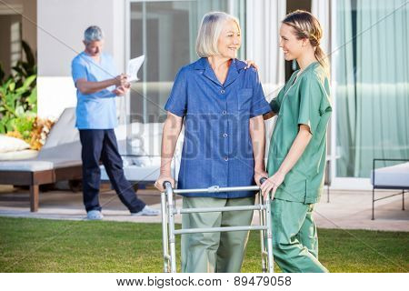 Friendly female nurse assisting senior woman to walk with Zimmer frame in lawn at nursing home