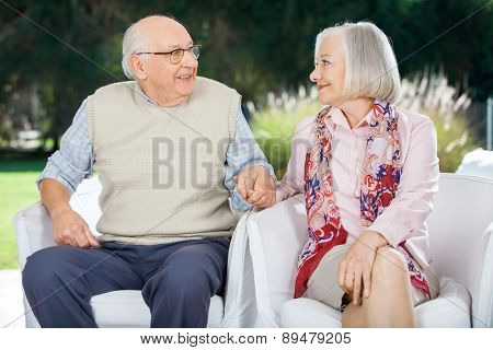 Senior couple holding hands and looking at each other while sitting on chairs at nursing home porch