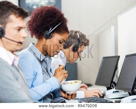 Young female customer service representative having food while colleagues working in office