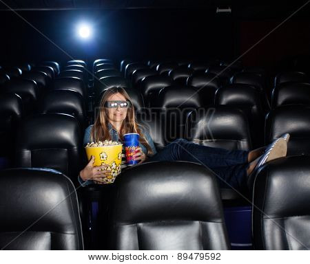 Woman with feetup on seat holding snacks while watching 3D movie at cinema theater