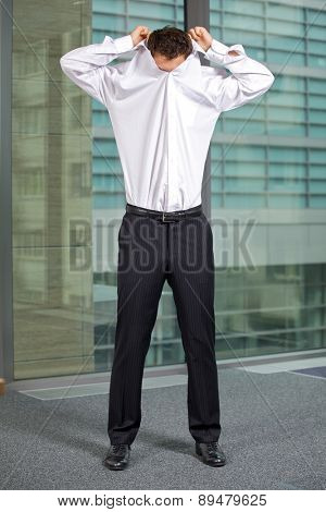 Businessman removing shirt at office