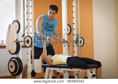 Young man helping a young woman lift a barbell on a bench