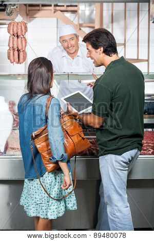 Couple with digital tablet buying meat at butchery