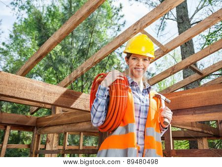Portrait of confident female construction worker holding pipe and hammer in timber cabin at site