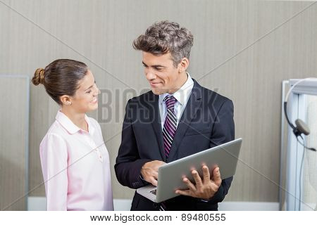Smiling manager and female call center employee using laptop in office