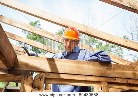 Portrait of confident male construction worker hammering nail on timber frame at site