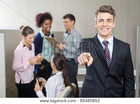 Portrait of smiling manager pointing at you while employees working in background at call center