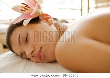 Young woman relaxing on massage table, eyes closed
