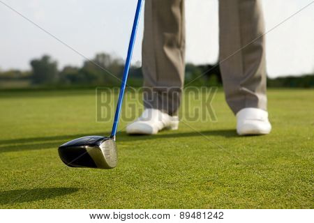 Person holding golf stick, low section