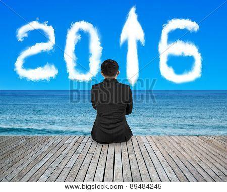 Businessman Sitting On Floor With 2016 Arrow Clouds Sky Sea
