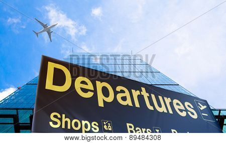 Departure sign and airplane in the blue sky