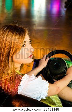 Beautiful girl in an electric bumper car at amusement park