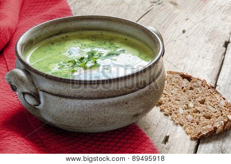 Green Vegetable Cream Soup  In A Ceramic Bowl On Rustic Wood