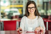 stock photo of pullovers  - Young beautiful smiling girl in glasses and white pullover sitting in urban cafe with a cup of coffee - JPG
