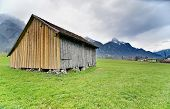 foto of snow capped mountains  - Lone wood cabin in the green Austrian countryside with snow - JPG