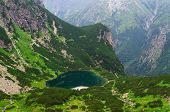 picture of emerald  - Picturesque view stretches over emerald pond and steep hillside in Tatra mountains Slovakia - JPG
