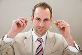 image of noise pollution  - Portrait Of Businessman With Yellow Earplugs In Office - JPG